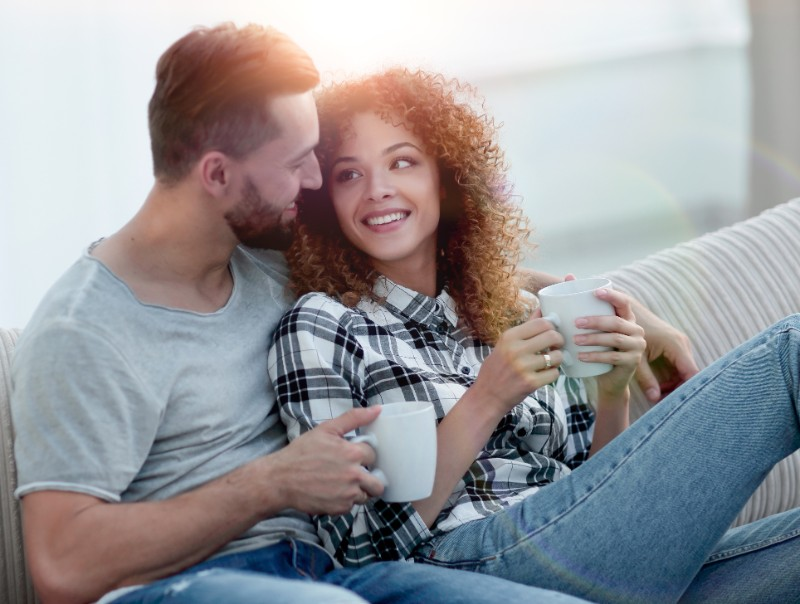 happy couple sitting on a sofa with coffee cups